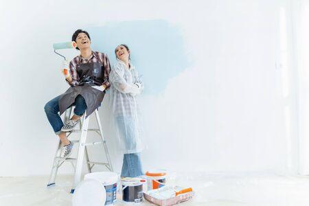 Des couples aident à peindre la nouvelle maison. Ils sont contents.