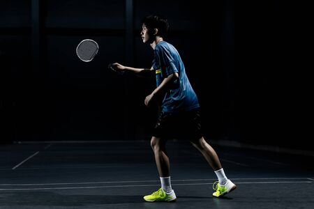 Asian badminton player is hitting in court