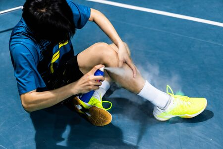 Asian badminton player is injured in the leg, he is cramping and using a spray