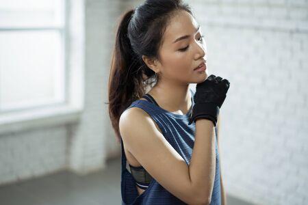 Asiatisches Mädchen, das im Fitnessstudio trainiert, hat sie müde und sie hat Schweiß im Gesicht.