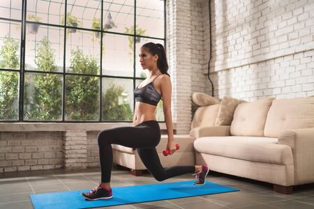 Asian woman  exercise at home. She's doing a leg lunge Stock Photo