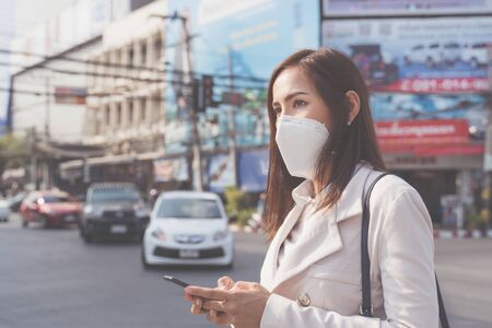 Asian woman  going to work.she wears N95 mask.Prevent PM2.5 dust and smog 写真素材