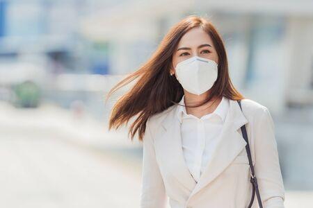 Asiatische Frau, die zur Arbeit geht. Sie trägt eine N95-Maske. Verhindern Sie PM2.5-Staub und -Smog
