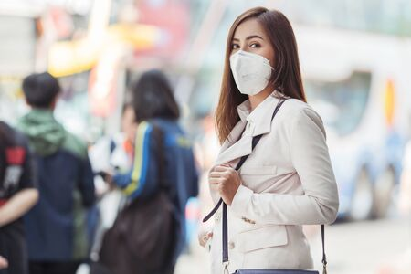 Asian woman are going to work.she wears N95 mask.prevent PM2.5 dust and smog. Reklamní fotografie - 129675780