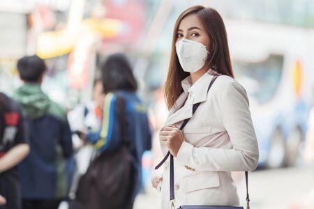 La donna asiatica sta andando al lavoro. Indossa la maschera N95. Previene la polvere e lo smog PM2.5. Archivio Fotografico