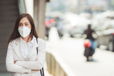 Asian woman are going to work.she wears N95 mask.prevent PM2.5 dust and smog. Foto de archivo - 129675778