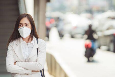 La mujer asiática va a trabajar. Lleva una máscara N95. Evita el polvo PM2.5 y el smog.