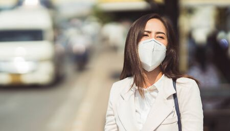 Asian woman are going to work.she wears N95 mask.prevent PM2.5 dust and smog 写真素材