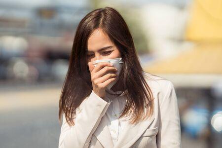 Une femme asiatique va travailler. Elle porte un masque N95. Empêche la poussière PM2.5 et le smog. Elle tousse