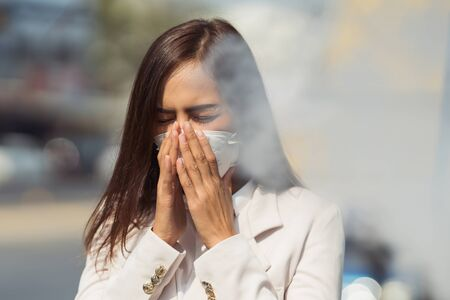 Una mujer asiática va a trabajar. Lleva una máscara N95. Evita el polvo PM2.5 y el smog. Está tosiendo