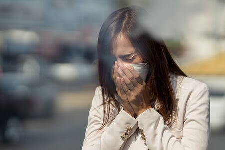 Asiatische Frau wird arbeiten. Sie trägt eine N95-Maske. Verhindern Sie PM2,5-Staub und Smog. Sie hustet