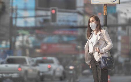 La donna asiatica sta andando al lavoro. Indossa la maschera N95. Previene la polvere e lo smog PM2.5 Archivio Fotografico