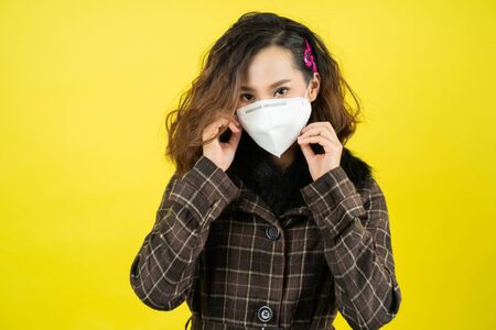 Asiatische Frau, sie trägt N95-Maske. Verhindern Sie PM2.5-Staub- und Smog-Studiokonzept