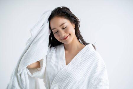 Asiatische Frau, die ein trockenes Handtuch verwendet, um ihr Haar zu trocknen. Nach dem Duschen Standard-Bild