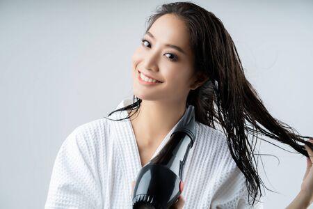 Mujer asiática secándose el cabello después de la ducha Foto de archivo
