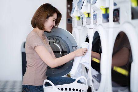 Aziatische vrouwen die kleren wassen bij de wasserijwinkel Stockfoto