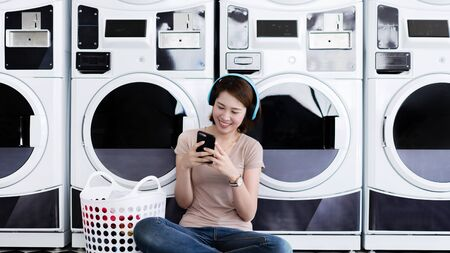 Asian women are listening to music at the laundry shop. Standard-Bild - 129776443