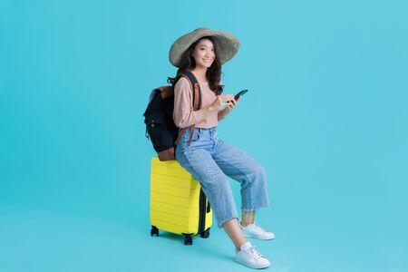 Azjatyckie kobiety turystów ona siedzi na lotnisku. Korzysta z telefonu komórkowego.
