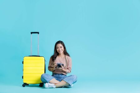 Asian women tourists with a yellow suitcase
