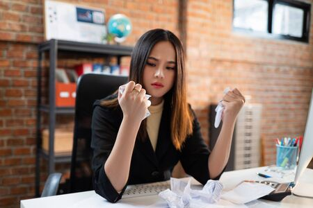 Asian businesswomen are failing from work. She crumpled the paper.
