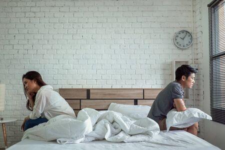 Las parejas asiáticas se pelean, se sientan en la cama, discuten para no hablar entre ellos. Son infelices Foto de archivo
