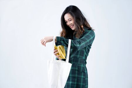 Asian woman buy vegetables from the supermarket. She uses a paper bag
