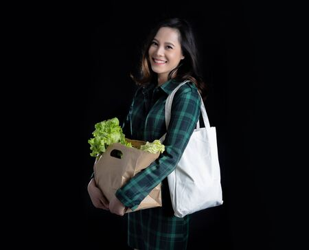 Asian woman use cloth bags and paper bags. To reduce the use of plastic bags