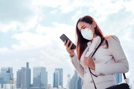 Una mujer asiática va a trabajar. Lleva una máscara N95. Evita el polvo PM2.5 y el smog. Foto de archivo