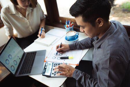 Les hommes asiatiques calculent les affaires, les revenus, les dépenses. Ils sont dans un café Banque d'images