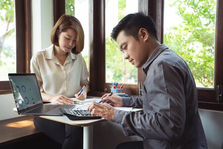 Asian men are calculating business, income, expenses. They are in a coffee shop 版權商用圖片 - 130051816