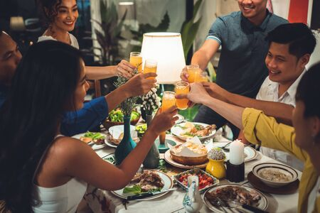 Asian people are eating dinner At home with friends, theyre happy Stock Photo