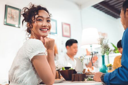 Asian people are eating dinner at home with friends, they are happy to talk.
