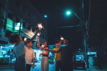 Asian friends group celebrating birthday party, they are playing fireworks Stock Photo