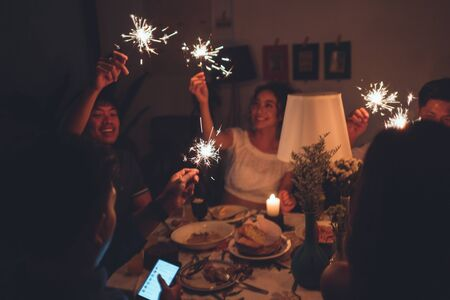 Asian friends group Celebrating in a party, they are playing fireworks Stock Photo