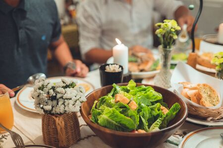 Group of people are eating dinner salads.
