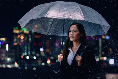 Business woman, she is going home, she covered by the umbrella.