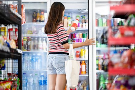 Woman choosing drinks from a freezer.