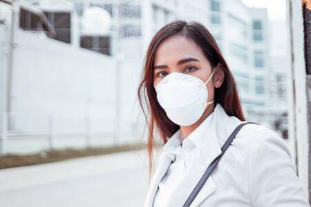 Asiatische Frau, die zur Arbeit geht. Sie trägt eine N95-Maske. Verhindern Sie Staub und Smog