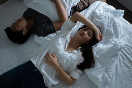 Asian couples are very stressed and they are lying on bed.