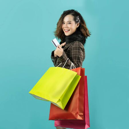 Asian woman are shopping in the winter, she is using a credit card and enjoys shopping.