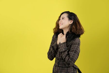 Asian woman, she is happy with a yellow background.