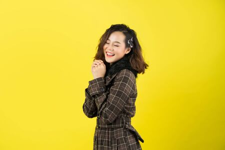 Asian woman, she is happy with yellow background. Stock fotó
