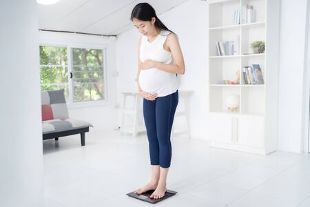 Pregnant woman weighs at home. Stock fotó