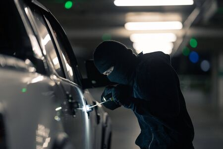Robbers are robbing cars. Parked in the night parking