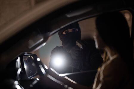 masked robber with a gun threatens a woman in a car. robbery.Parking at night