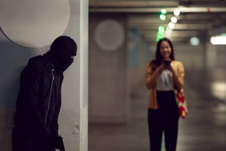 Robber attack lonely woman in the dark parking area