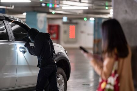 Woman is calling the police. The thief was leverage her car at the parking lot at night.