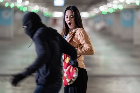 The thief is stealing the womans bag in the car park at night Stock fotó