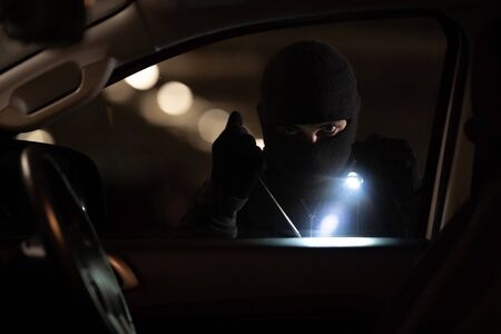 The robbers robbed the car in the parking lot at night.