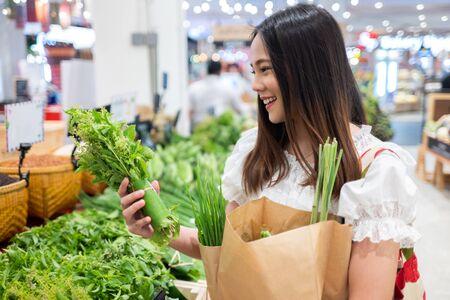 Aziatische vrouw koopt groenten in de supermarkt. Ze gebruikt papieren tassen en geweven tassen. Voor het milieu Stockfoto